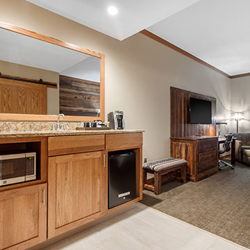 What amenities are available in the guestrooms of Norfolk Lodge & Suites